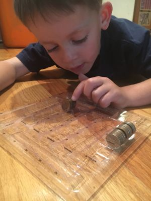 My son was so focused as he counted his coins carefully.
